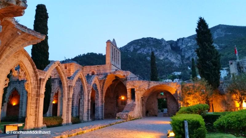 Kloster, kirkeruiner og klosterhagen til Bellapais abbey med lysene tent i skumringen. Fjellene i bakgrunnen.