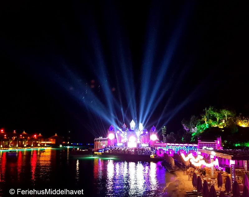 Et slott som ligger ved vannet med et lysshow som lyser opp mot himmelen. Cage club,Port Cratos kyrenia.