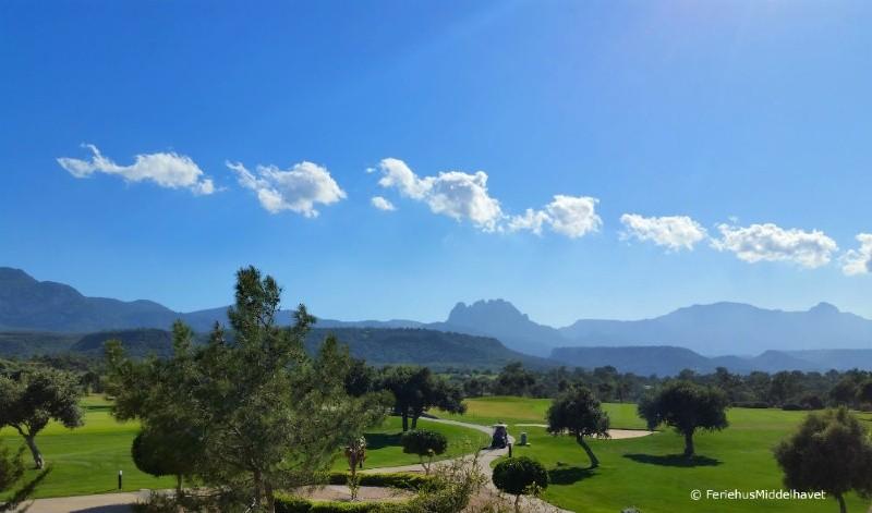 Esentepe og Bahceli østenfor Kyrenia Korineum 18.hulls golfbane med caddy på vei mellom oliven trær. Besparmak fjellene i bakgrunnen.