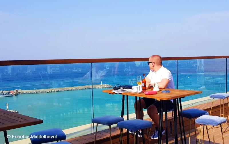 Ung mann ser ut over turkis hav fra en skybar Lords Hotel. Drikker en øl.