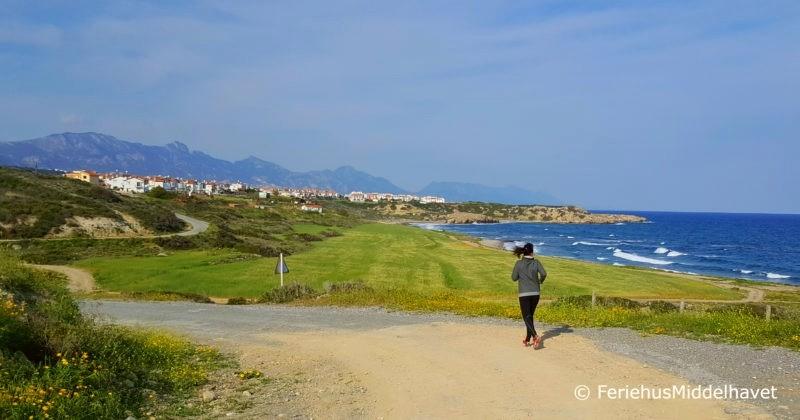 Dame som jogger på den gamle kystveien mellom Esentepe og Bahceli østenfor Kyrenia Nord Kypros.  bak, blomster i grøften og MIddelhavet. I bakgrunnen sees Sea Magic Park anlegget og Besparmak fjellene.