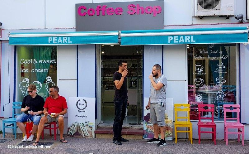 """To menn som sitter og spiser is på fortøauet utenfor en coffeeshop. """" andre menn står og røyker."""