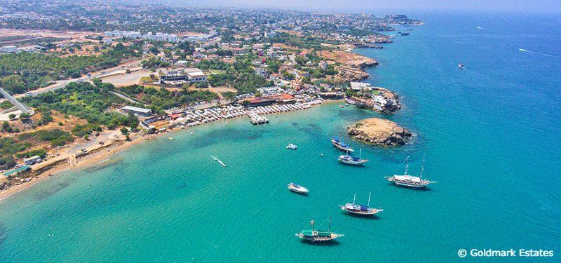 Escape Beach Alsancak Kyrenia Nord Kypros sett ovenifra med badebåter liggende og landskapet bak.