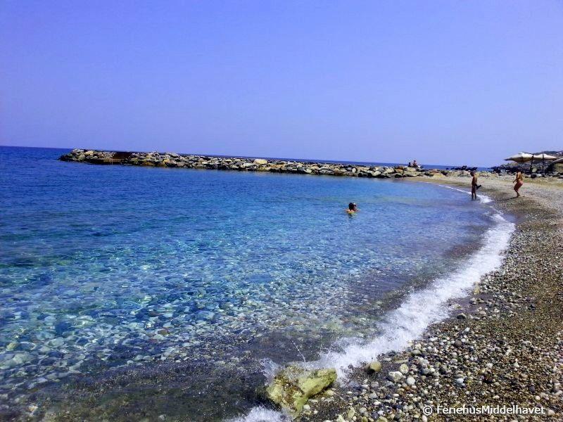 Krystall klart vann på Korineum beach club ved Esentepe-og-bahceli-østenfor-kyrenia. Stranden har noe småstein og en bademolo.