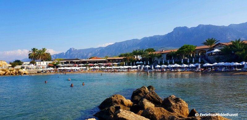 Denizkizi strandklubb med havet foran stranden med solsenger, kafeen bak og helt bakerst fjellryggen Besparmak.