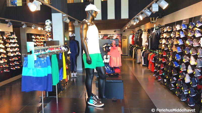 Fra en Adidas butikk Kyrenia Nord Kypros.. Utstillingsdukke med sportsklær, rader med løpesko og et stativ fult med shortser.
